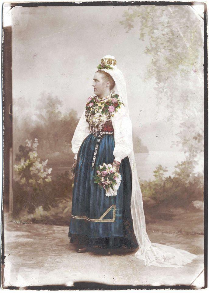 Handkolorerat foto av en brud i Leksandsdräkt. Fotot taget i en atelje med målad bakgrund. Fotot är från någon gång mellan 1870-1910.