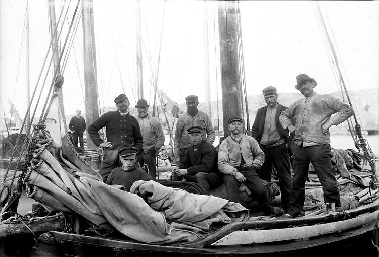 Ett fiskelag vid kajen i Marstrand, Bohuslän. De ser mycket stolta ut när de poserar. Men att fiska var förr förenat med stora risker. När man tittar i dödböckerna i församlingar längs kusten är det inte ovanligt med flertalet som drunknat när deras skepp förlist. Förr var döden alltid närvarande i samhället eftersom så många dog som barn, men vid kusten fanns en extra dimension då döden även ofta kunde komma på havet.